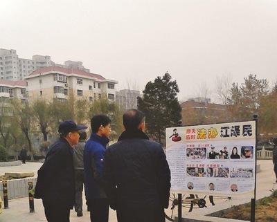 Pejalan kaki melihat poster di Kota Shijiazhuang, Provinsi Hebei.