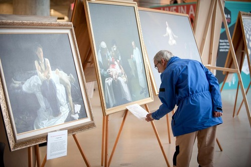 "Pengunjung membaca keterangan lukisan ""Kejahatan Organ"" karya Xiqing Dong"