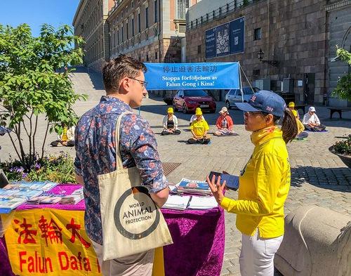 Practicanți prezintă Falun Dafa publicului în Piața Mynttorget pe 13 iunie 2020.